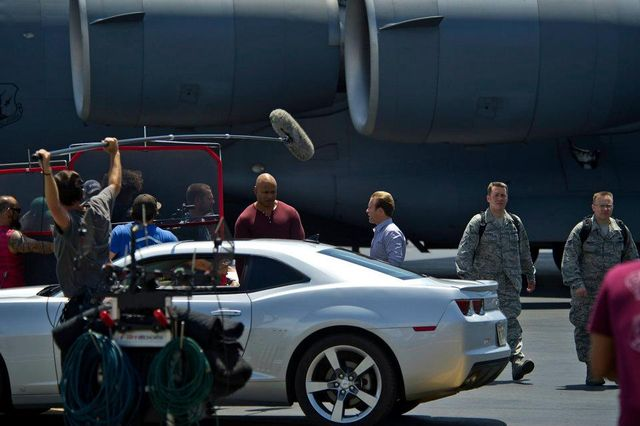 Actors Chris O'Donnell, LL Cool J, and Scott Caan of NCIS Los Angeles, and Hawaii Five-0 act out a scene during a recent episode of the CBS hit show Hawaii Five-0 at Joint Base Pearl Harbor-Hickam on March 26, 2012. U.S. Air Force Airmen and Hawaii Army National Guard Soldiers were cast as background extras during the filming. (Department of Defense photo by U.S. Air Force Tech. Sgt. Michael R. Holzworth/Released) Public Domain